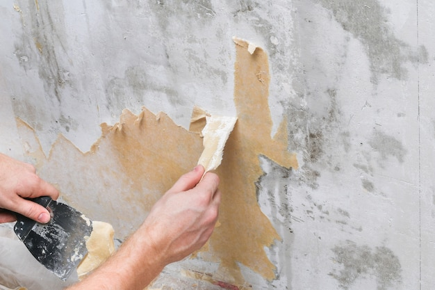 A man removes old wallpaper with a spatula and spray bottle with water.