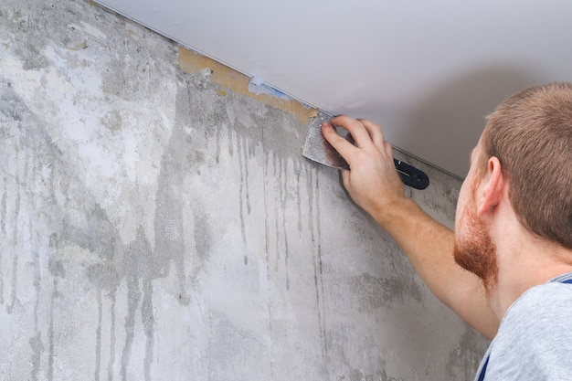 A man removes old wallpaper with a spatula and spray bottle with water