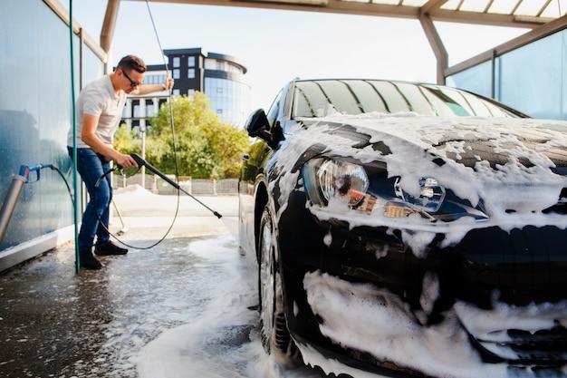 Uomo che rimuove la schiuma da un'auto