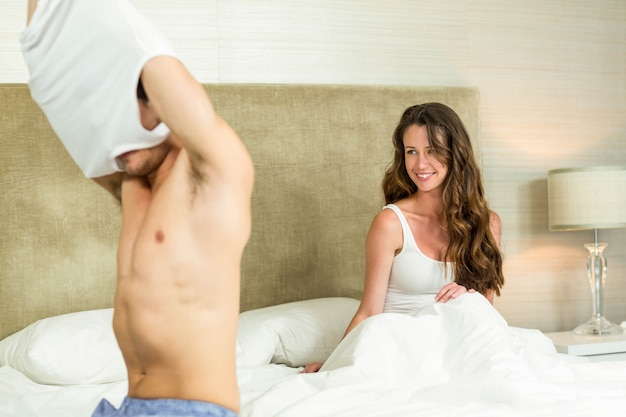 Man removing his vest in front of woman in bedroom