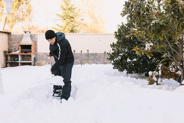 Man removing snow from the garden of his house with a shovel