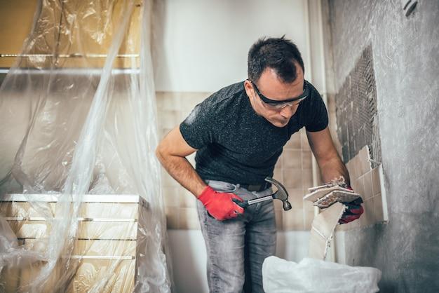 Man renovating kitchen tiles