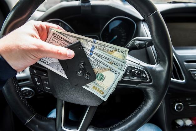 Человек арендует автомобиль для поездки и держит долар и автомобильный ключ. финансовая концепция