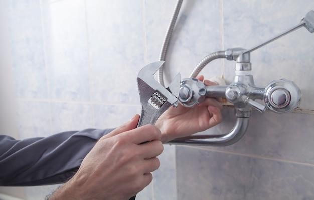 バスルームのシャワーの蛇口を修理して修理する男性。