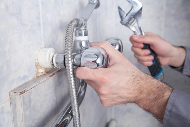 男は浴室のシャワーの蛇口を修理し、修理します。