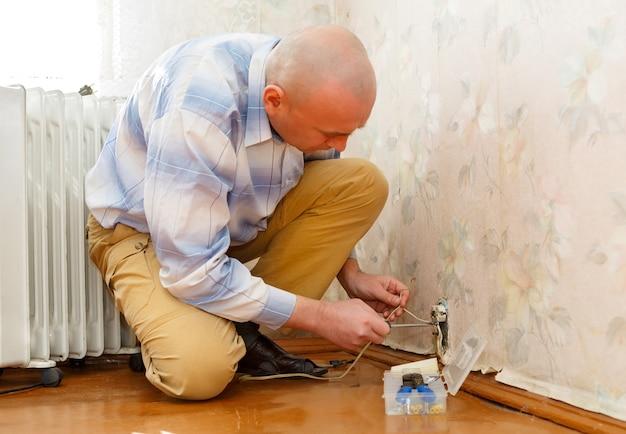 바닥에 앉아있는 동안 전기 콘센트를 수리하는 남자