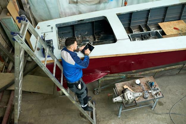 Man repairing boats in customs workshop