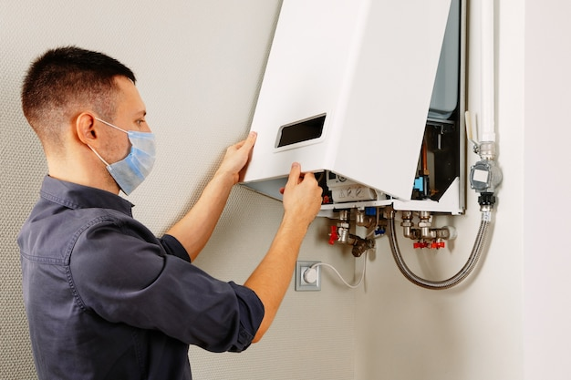 A man repairing a boiler in a medical mask