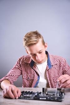 Человек ремонтирует сломанный компьютер, видеокарту, оперативную память, кулер, процессор, жесткий диск. молодой мастер работает с отверткой в сервисном центре.