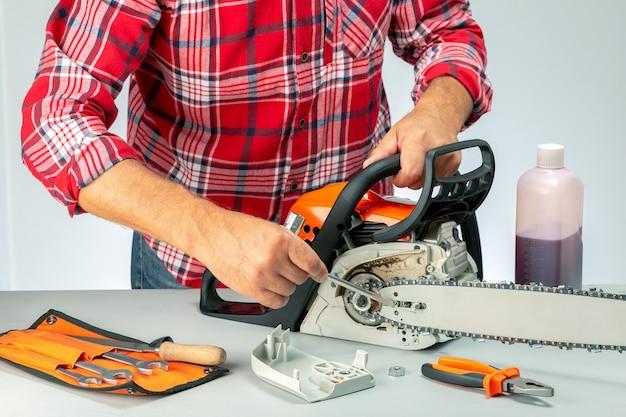 Man repairing chainsaw  in a workshop