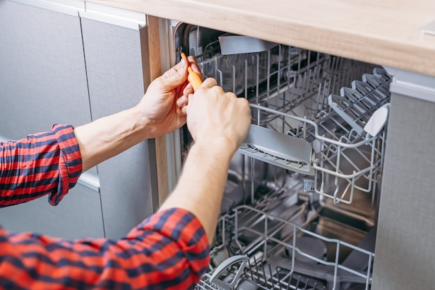 Man repairing dishwasher. male hand with screwdriver installs kitchen appliances
