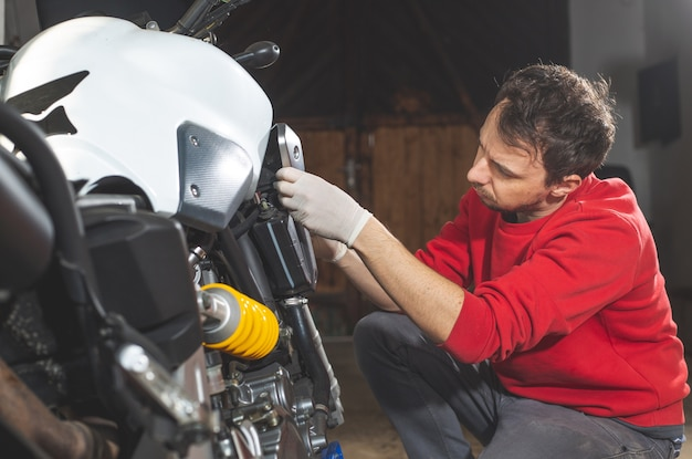 Man repairing, doing maintenance of his motorcycle, motorbike in the garage, reapir concept