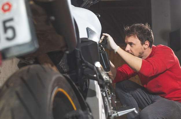 Человек ремонтирует, делает техническое обслуживание своего мотоцикла, мотоцикла в гараже, концепция reapir