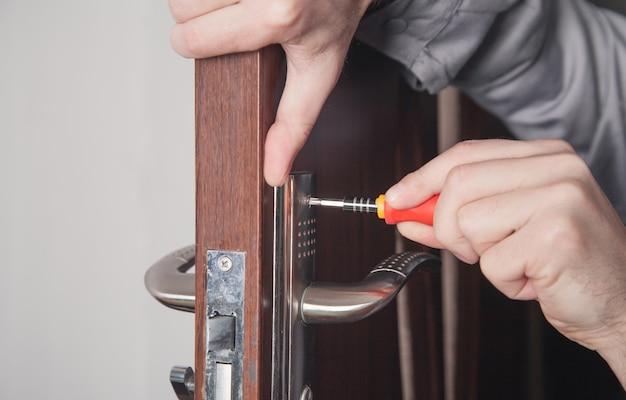 Мужчина ремонтирует дверной замок. рука мастера с отверткой