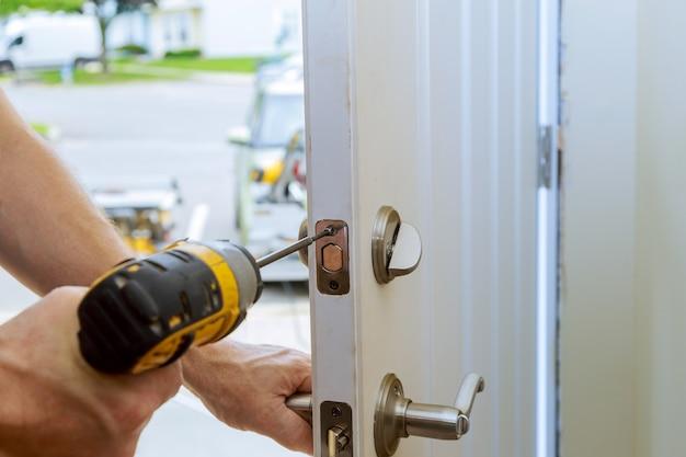 Man repairing the doorknob. closeup of worker's hands installing new door locker