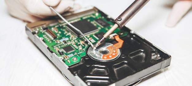 Человек ремонтирует жесткий диск. внутренние детали старого персонального компьютера. сломанный пк. паяльник в руках.