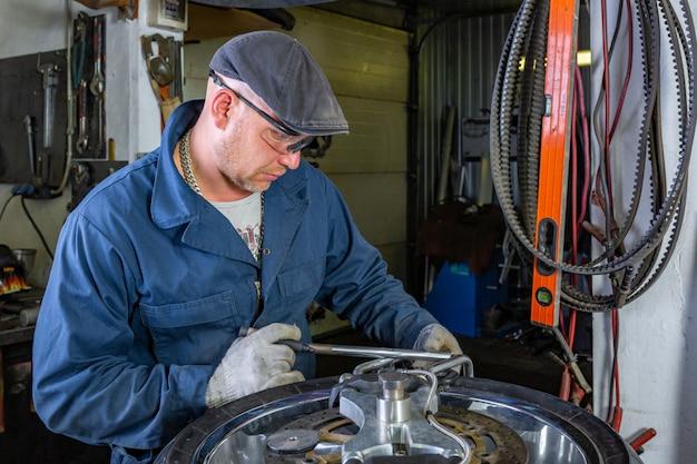 修理キット、チューブレスタイヤのタイヤプラグ修理キットでオートバイのタイヤを修理する男。