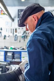 男は修理キット、チューブレスタイヤのタイヤプラグ修理キットでオートバイのタイヤを修理します。