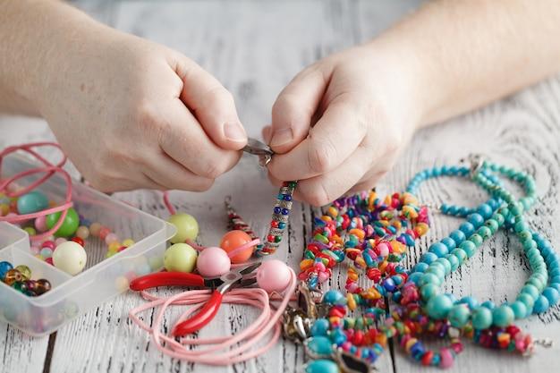 Человек ремонтирует или создает ювелирную серебряную цепочку с помощью плоскогубцев