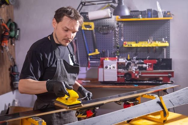 A man repairing the ski in the service
