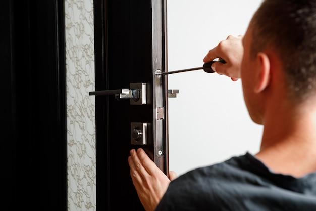 손잡이를 수리하는 남자. 문 손잡이 나무 문 밖으로 잠금 설치 작업 목수