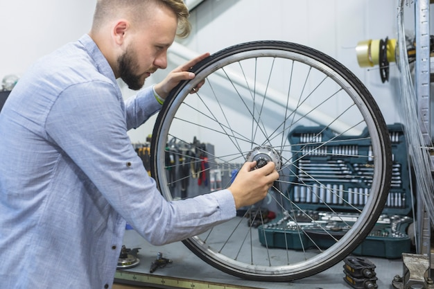 Man repairing wheel of bicycle in workshop