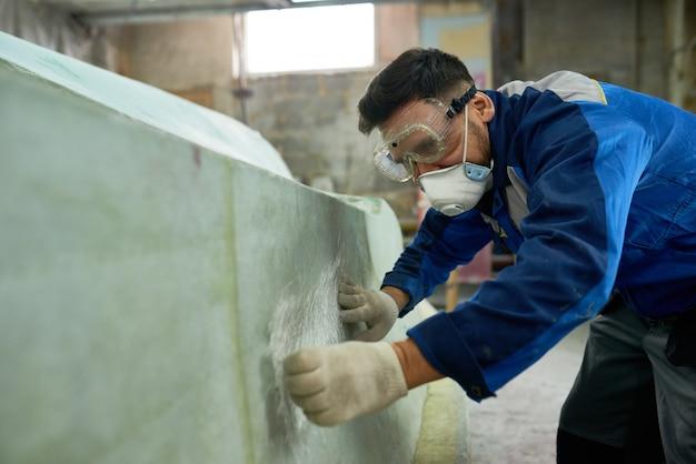 Человек ремонтирует яхты в мастерской