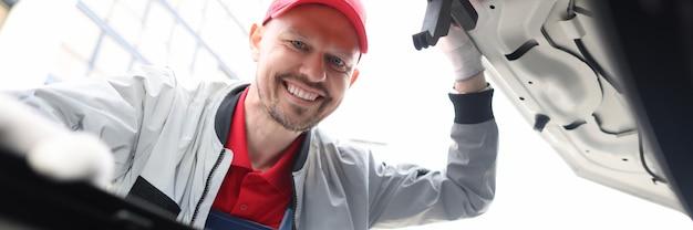Man repairman looking under hood of car