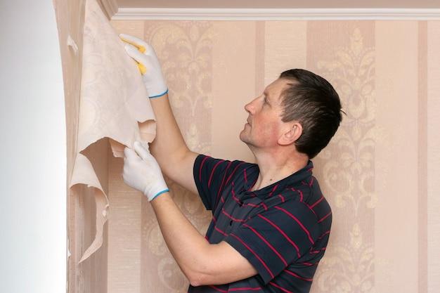 男、修理工が壁から古い壁紙を取り除き、壁紙を交換する