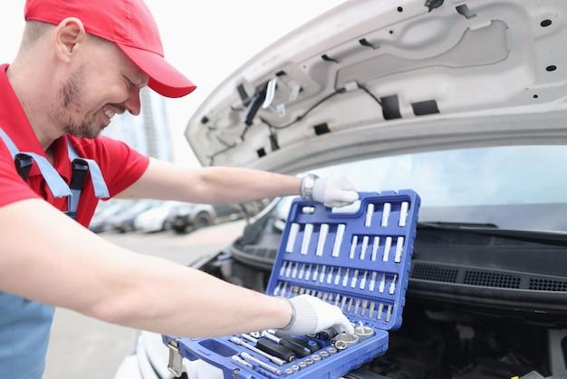 Ремонтник человек берет инструменты из чемодана на открытом капоте автомобиля