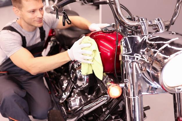 ぼろきれのオートバイサービスコンセプトでオートバイのタンクを拭く男の修理工