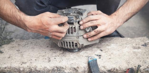男は車のオルタネーターを修理します。サービスセンター