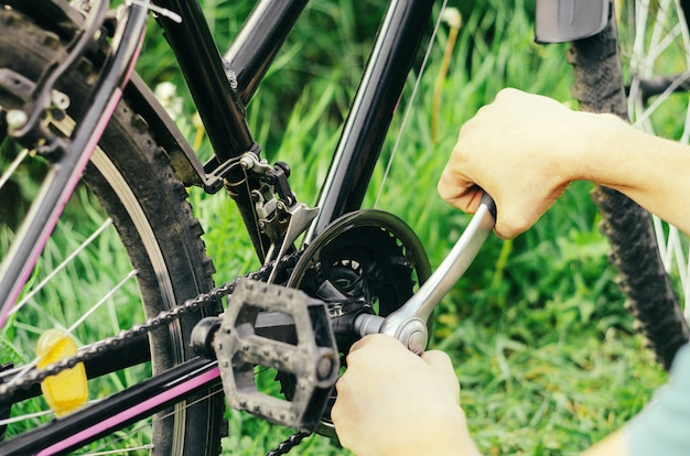 A man repairs a chain on a mountain bike with a socket wrench on the grass.
