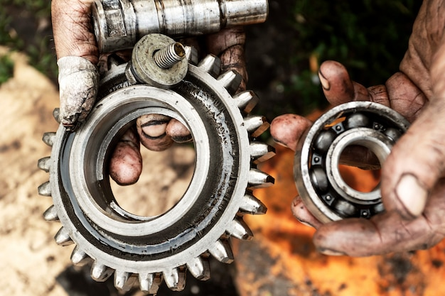 Man repairs engine of tractor, agricultural machinery. bearings in dirty hands.