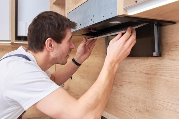 Мужчина ремонтирует вытяжку на кухне. сменный фильтр в вытяжке