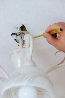 男は家の中でドライバーを使って白いシャンデリアを修理、取り付け、取り外します。シャンデリアの修理、設置、取り外しのサービス。露出したワイヤーでぶら下がっている分解されたシャンデリア