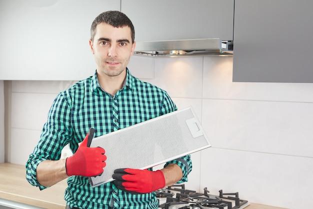 男は台所のレンジフードを修理します。炊飯器フードの交換用フィルター。