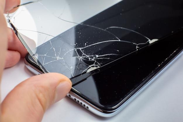 スマートフォン用の壊れた強化ガラススクリーンプロテクターを交換する男。閉じる。