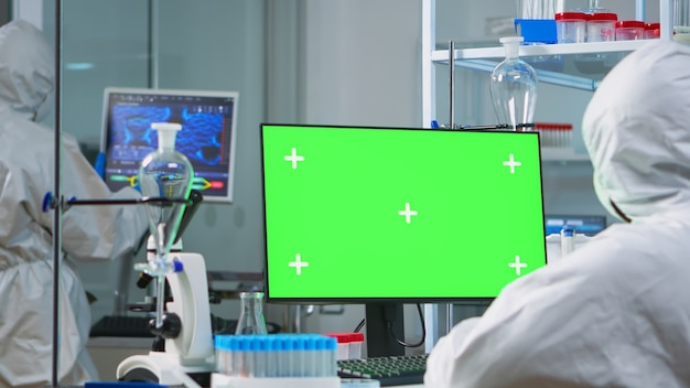 현대적인 장비를 갖춘 실험실에서 크로마 키 컴퓨터를 보고 있는 작업복을 입은 남자 연구원. 백신 연구를 하는 미생물학자 팀은 녹색 화면, 격리된 모형 디스플레이가 있는 장치에 글을 쓰고 있습니다.
