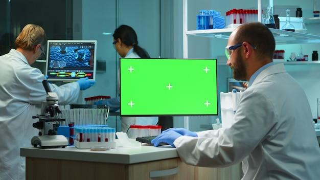 초과 근무를 하는 현대적인 장비를 갖춘 실험실에서 크로마 키 컴퓨터를 보고 있는 남자 연구원. 백신 연구를 하는 미생물학자 팀은 녹색 화면, 격리된 모형 디스플레이가 있는 장치에 글을 쓰고 있습니다.