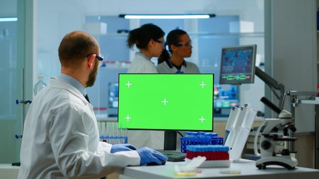 컴퓨터에 타이핑하는 현대적인 실험실에서 크로마 키 디스플레이를 보고 있는 남자 연구원. 백신 연구를 하는 미생물학자 팀은 녹색 화면, 격리된 모형 디스플레이가 있는 장치에 글을 쓰고 있습니다.