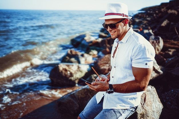 The man at the resort in a white shirt and hat sitting on a rock on the sea.