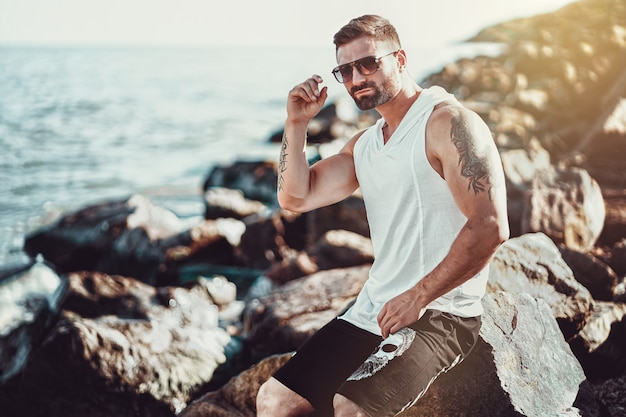The man at the resort in a white shirt and sunglasses sitting on a rock on the sea