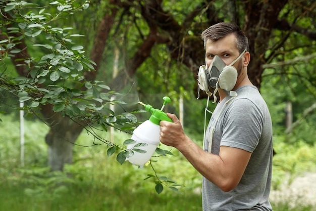 The man in the respirator sprinkles the plants.