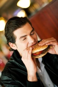 Man in restaurant eating hamburger