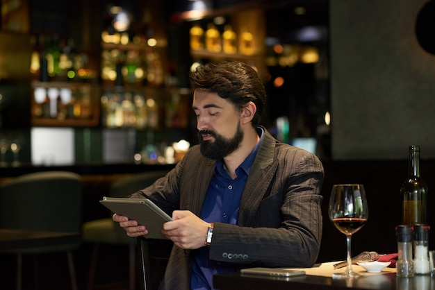 Man in restaurant reading news online