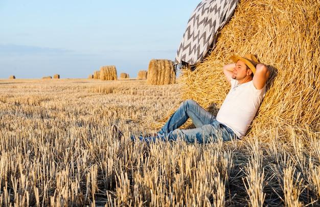 Man resting after hay harvesting in haystacks