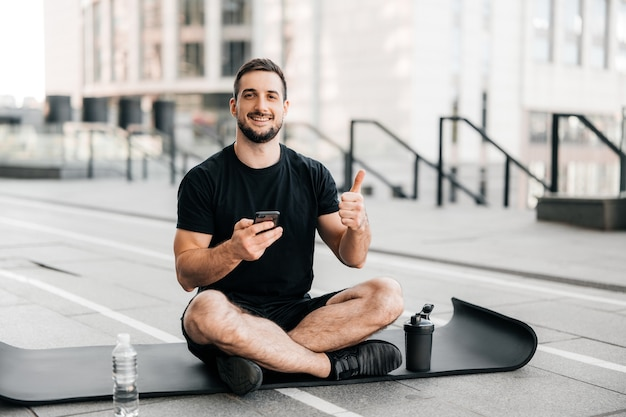 Man resting after outdoors excercising with smartphone in hand and thumbing up. sports water bottle on black yoga mat. sporty man after practicing yoga, relaxing on mat, texting on phone.