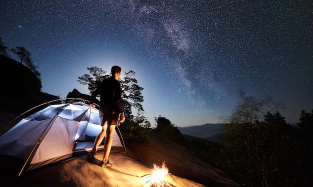 夜のキャンプの横で休んでいる男