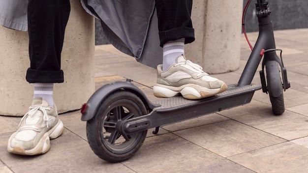 Uomo che riposa il suo piede su uno scooter elettrico all'aperto